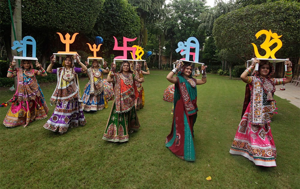 Women dressed in traditional finery carry religious symbols on their heads as they practice the Garba dance ahead of the Navratri festival in Ahmadabad.