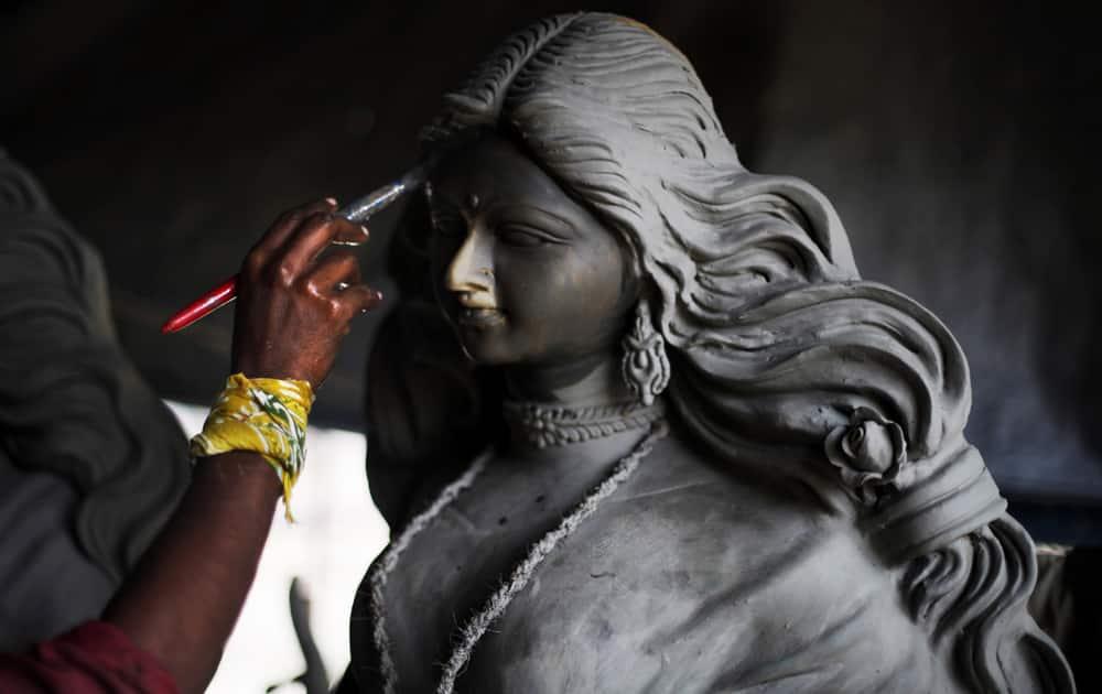Artist prepares an idol of Hindu goddess Durga ahead of Durga Puja festival in New Delhi.