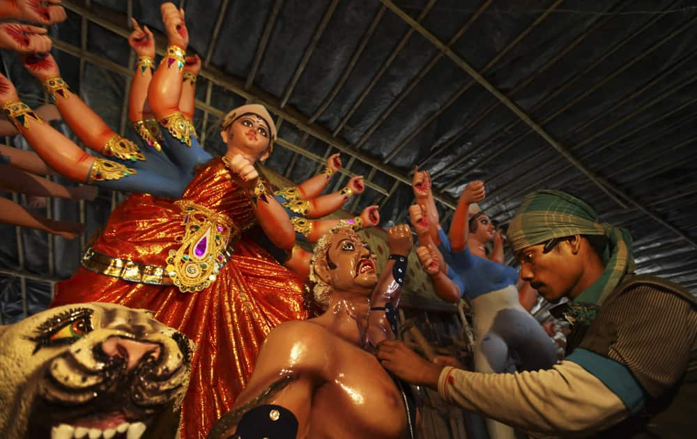 Artist works on idols of Hindu gods and goddesses in his workshop ahead of the Durga Puja festival, in New Delhi.
