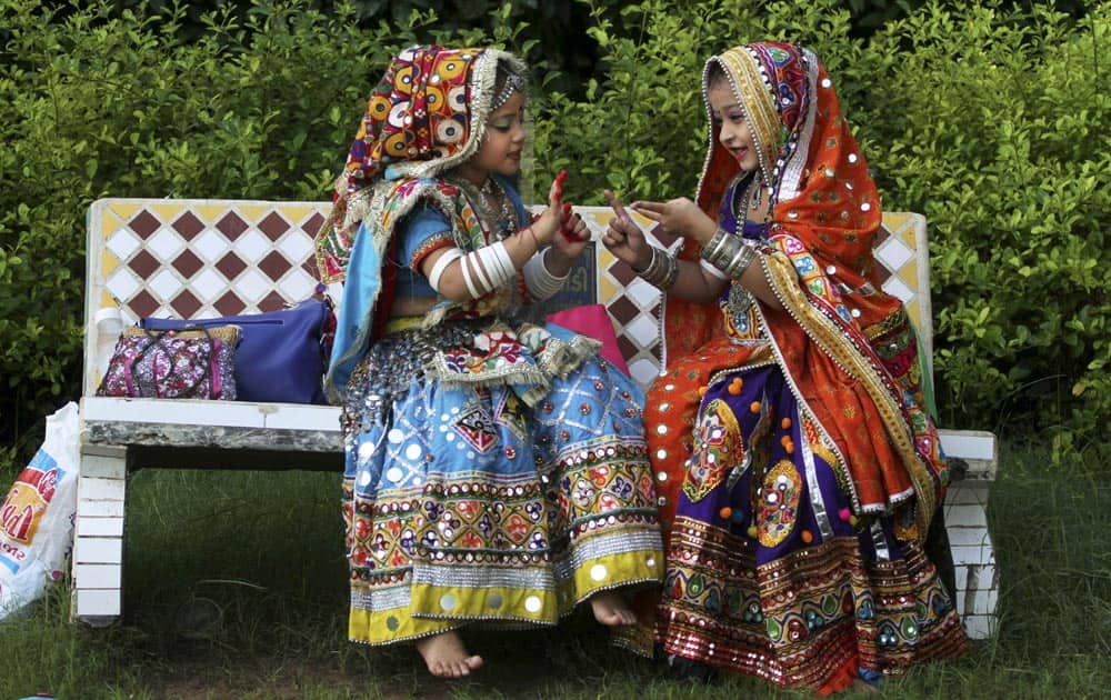 Young Indian girls dressed in traditional attire play with each other as others practice Garba, a form of dance from the west Indian state of Gujarat.