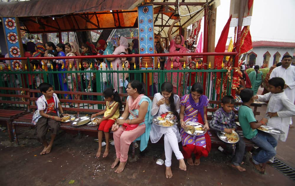 Hindu devotees eat holy food as others stand in a queue to offer prayers at a Hindu goddess Kali temple on the second day of the Navratri festival in Jammu.
