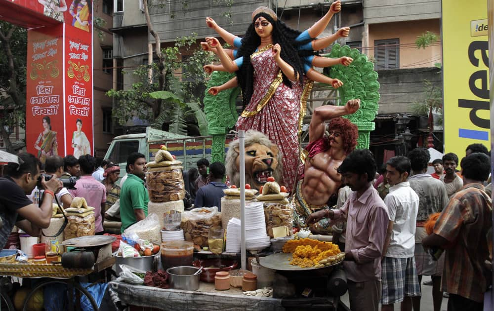 An idol of Hindu goddess Durga is transported past a snack vendor to a venue of worship in Kolkata.