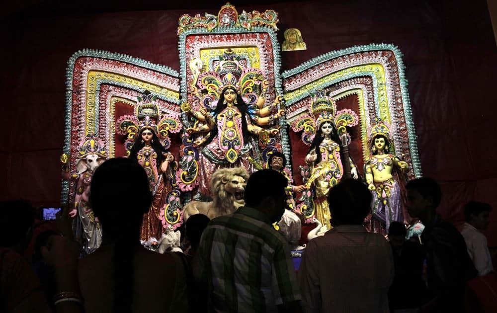 Devotees watch idol of decorated Hindu goddess Durga during Durga Puja festival, in Kolkata.