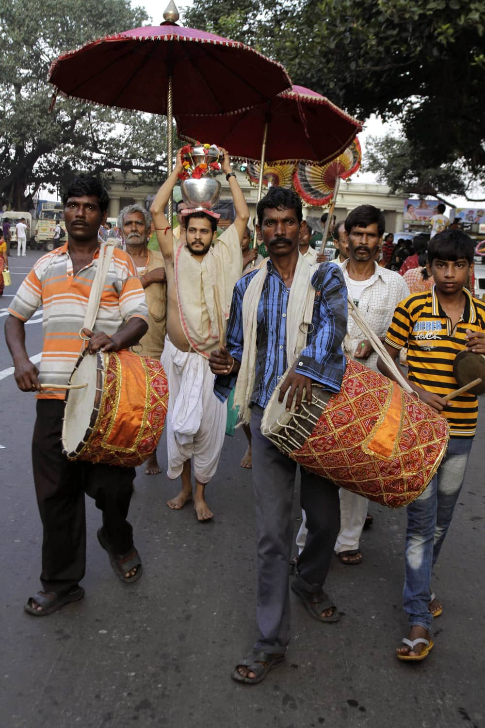 A devotee carries holy water from the Ganges River as he marches through a street in a procession of Hindu festival Durga Puja in Kolkata.