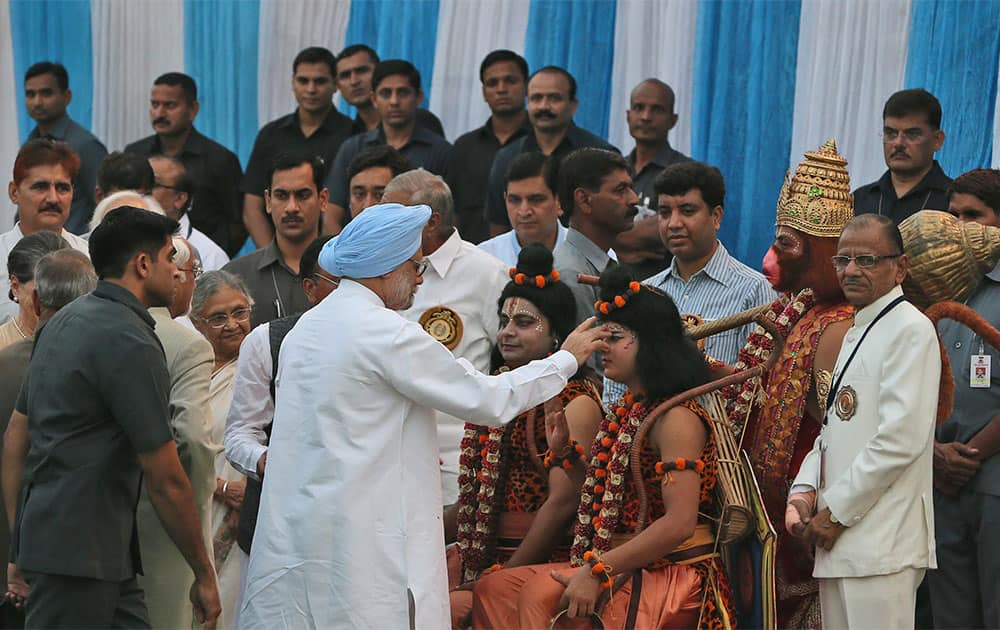 Prime Minister Manmohan Singh, blue turban, performs a ritual before people dressed as Hindu deities Ram, Lakshman and Hanuman during Dussehra celebrations in New Delhi.