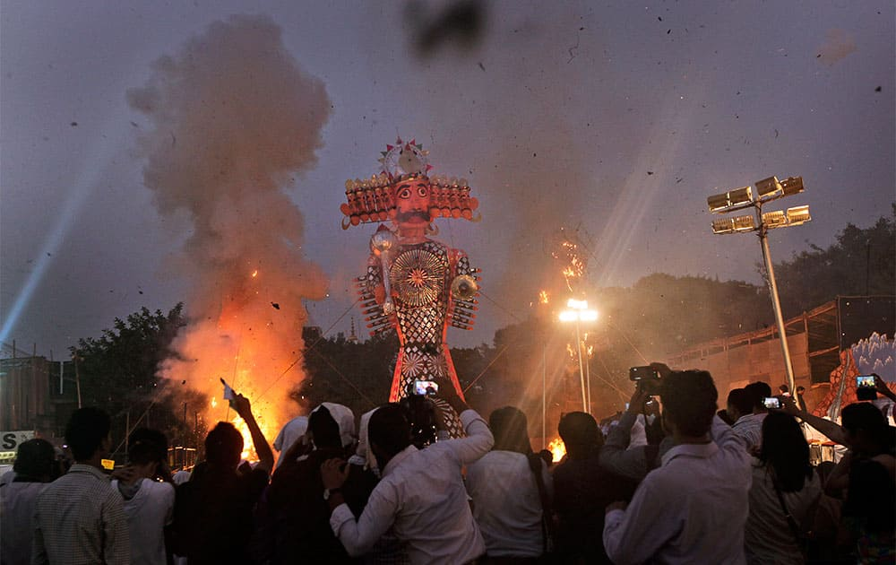 People watch as effigies of the ten-headed demon king Ravana and his brothers are burned during Dussehra celebrations in New Delhi.