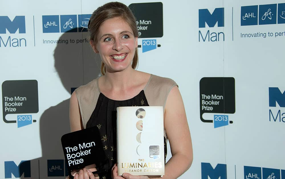 New Zealand author Eleanor Catton poses after being announced the winner of the Man Booker Prize for Fiction, holding her prize and her book for the photographers, in central London.