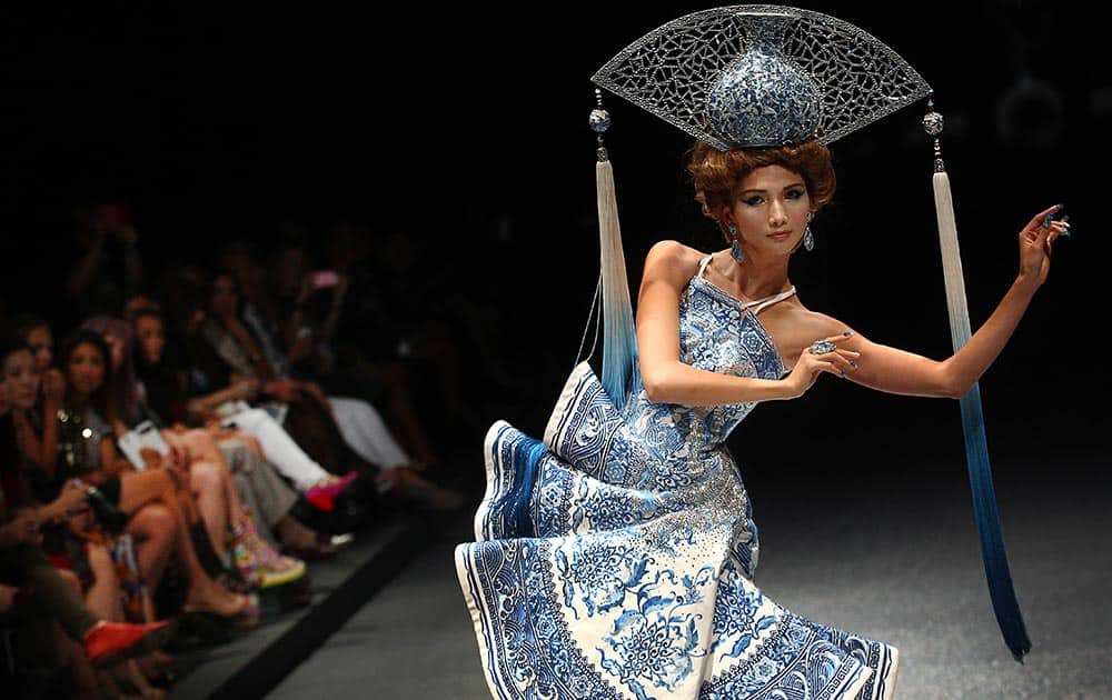 A model showcases an outfit by Chinese fashion design Guo Pei, in Singapore during the Fide Fashion Week 2013 Asian Couture show.