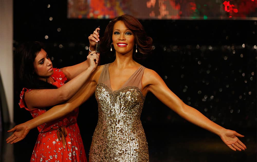 A Madame Tussauds worker adjusts the hair of a wax figure of late US singer Whitney Houston, as she poses for the photographers, during a photo-op in London.