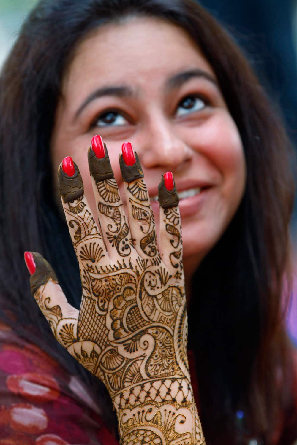 A woman dries her hand after getting it painted with henna on the eve of Hindu festival 'Karwa Chauth' in Allahabad.