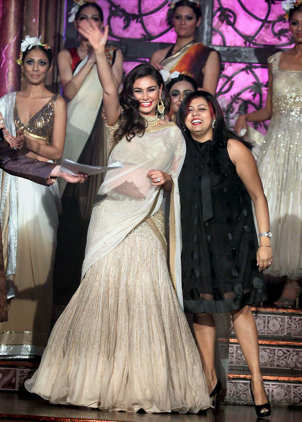 Actress Lisa Ray showcasing a saree collection at a fashion show in New York.
