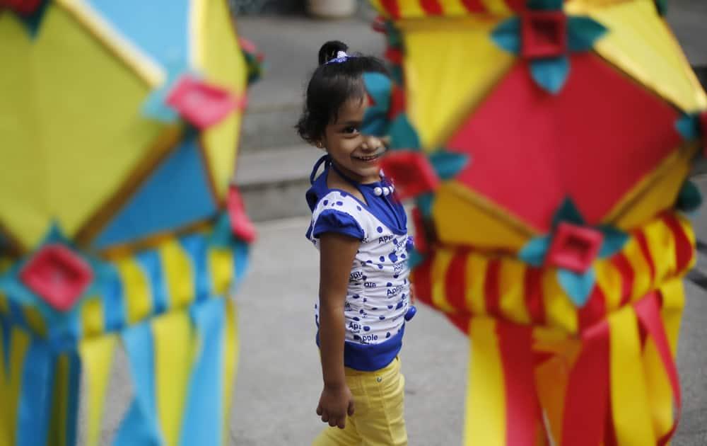 A girl smiles as shewalks past lanterns hung at a roadside stall ahead of Diwali in Mumbai.
