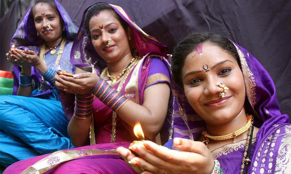 Artists pose with 'diya' during an event to celebrate Diwali in Mumbai.