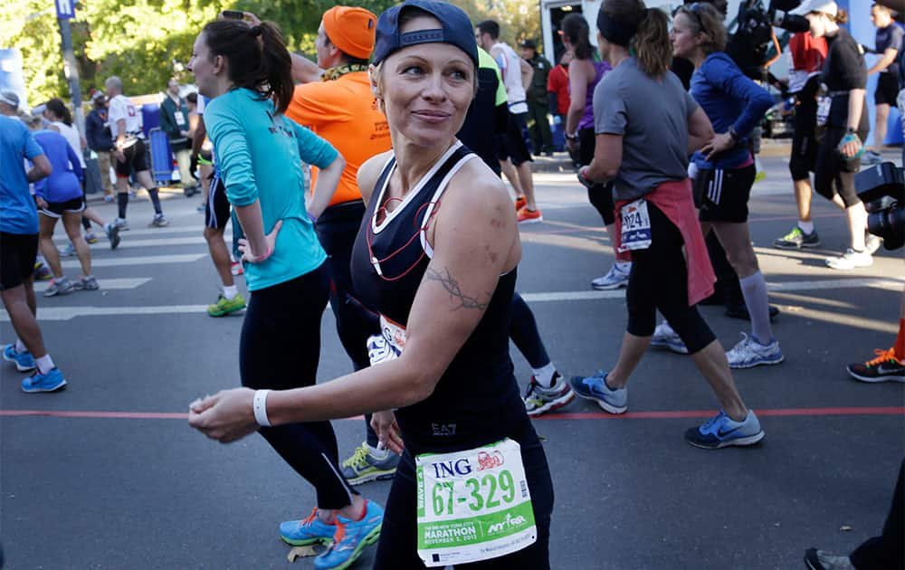 Actress Pamela Anderson smiles after crossing the finish line at the 2013 New York City Marathon in New York.