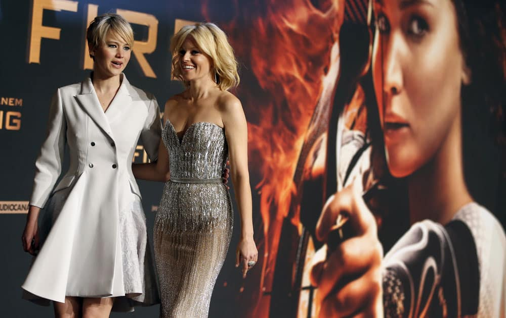 Actresses Elizabeth Banks, right, and Jennifer Lawrence, both from the US, pose for photographers as they arrive at the German premiere of their movie
