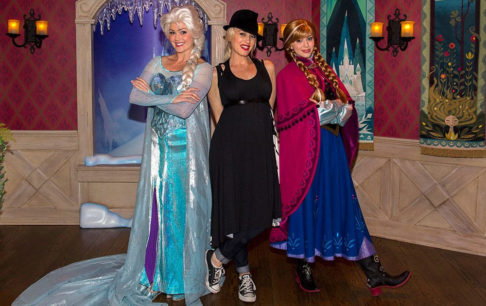This image released by Disneyland shows musician Gwen Stefani, center, posing with women dressed as Elsa the Snow Queen, left, and Anna from the Disney animated film,