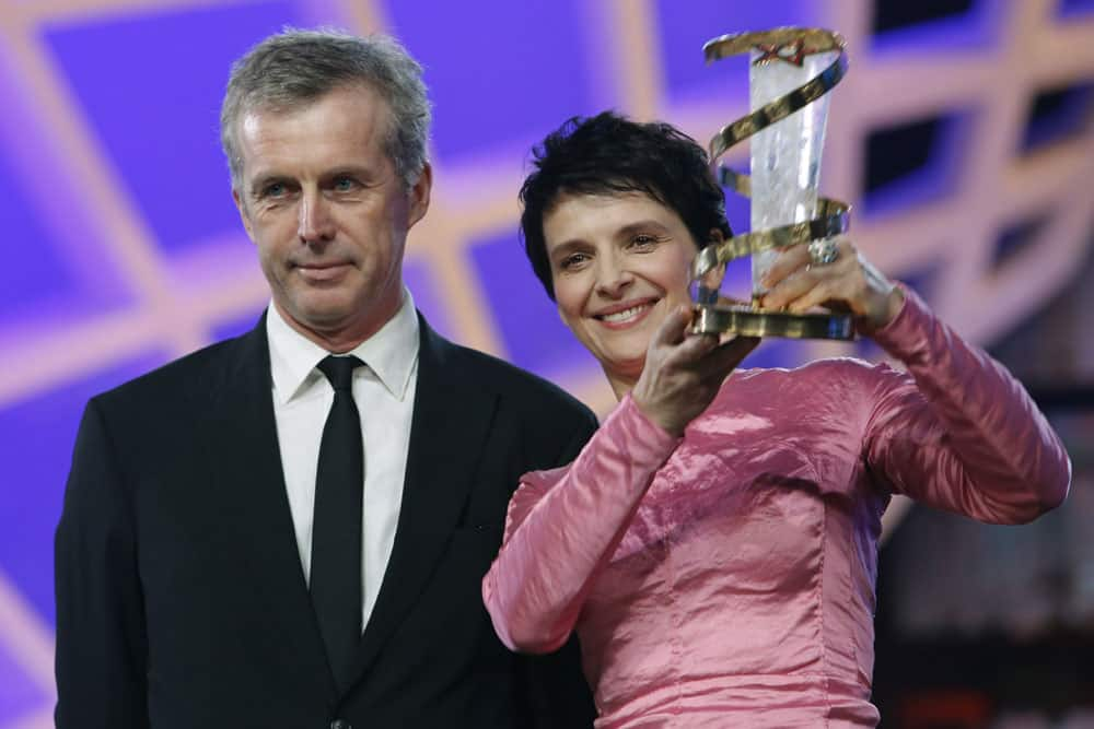 French actress Juliette Binoche poses after receiving a trophy in tribute to her lifetime career from French director Bruno Dumont, left, at the Marrakech International Film Festival.