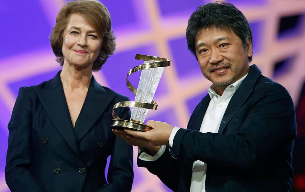 Japanese director, screenwriter, and producer Hirokazu Koreeda receives a trophy in tribute to his lifetime career from British actress Charlotte Rampling, left, at the Marrakech International Film Festival.