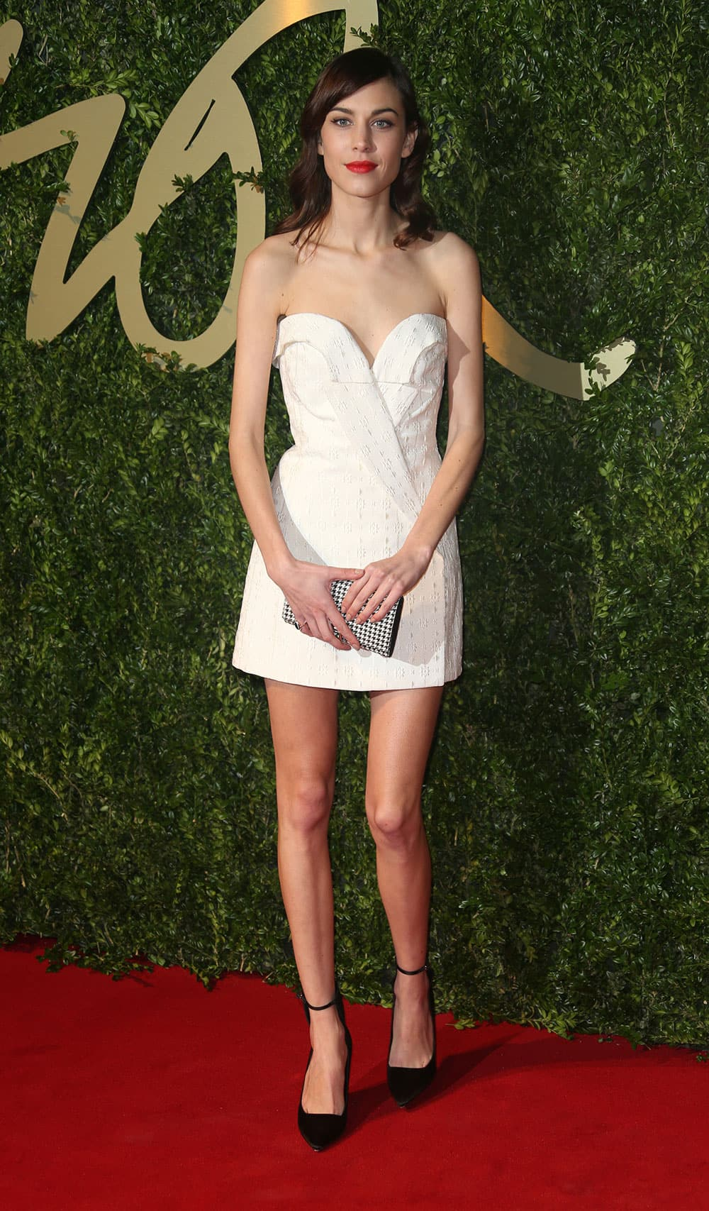 British model and presenter Alexa Chung poses for photographers as she arrives for the London Coliseum for the 2013 British Fashion Awards, in central London.