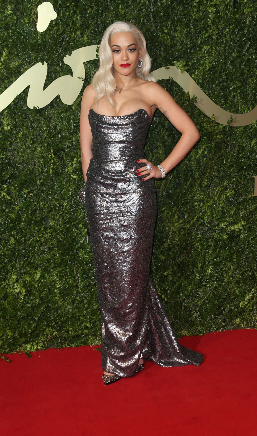 British singer Rita Ora poses for photographers as she arrives for the London Coliseum for the 2013 British Fashion Awards.