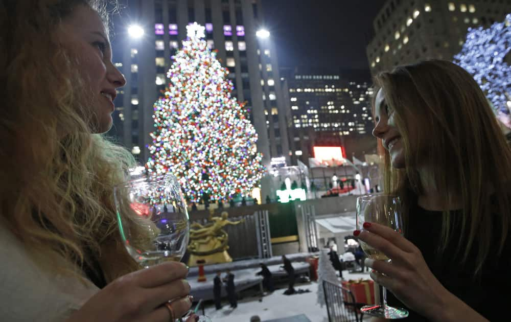 Anna Ladner and Vanja Ojes Dahlberg sip Champagne in front of the Rockefeller Center Christmas tree after it was lit, in New York.