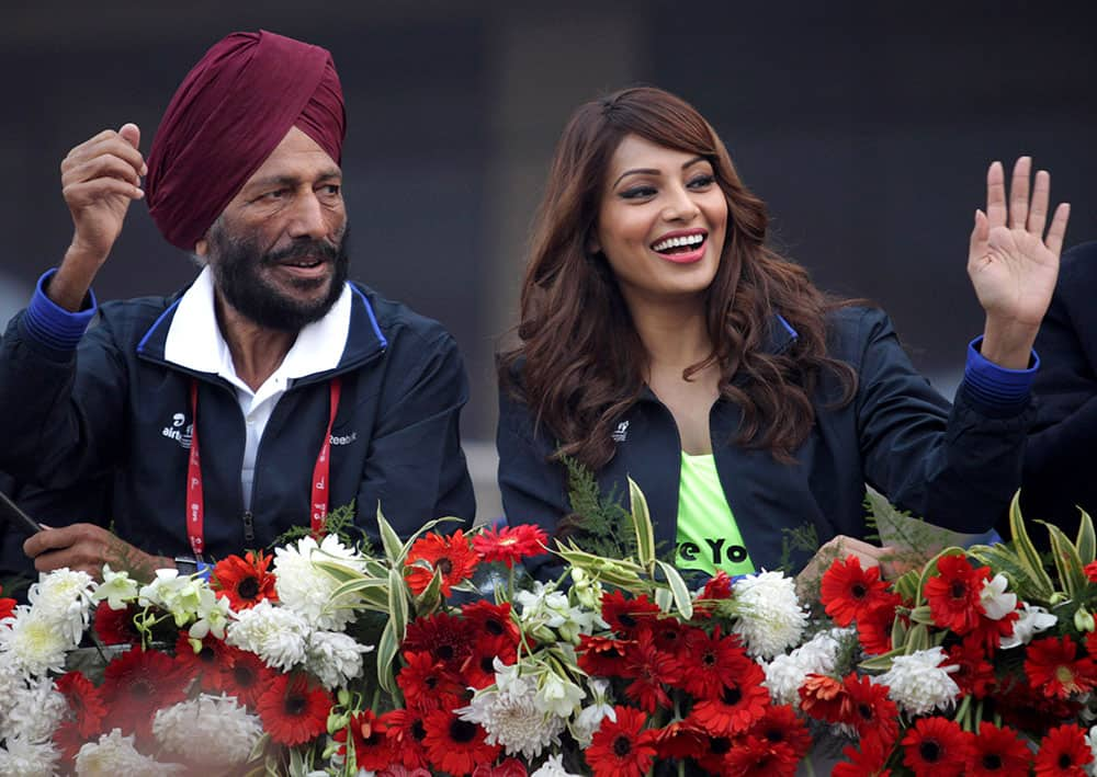 Former Indian athlete Milkha Singh and Bollywood actor Bipasha Basu wave to the participants during the Delhi Half Marathon in New Delhi.