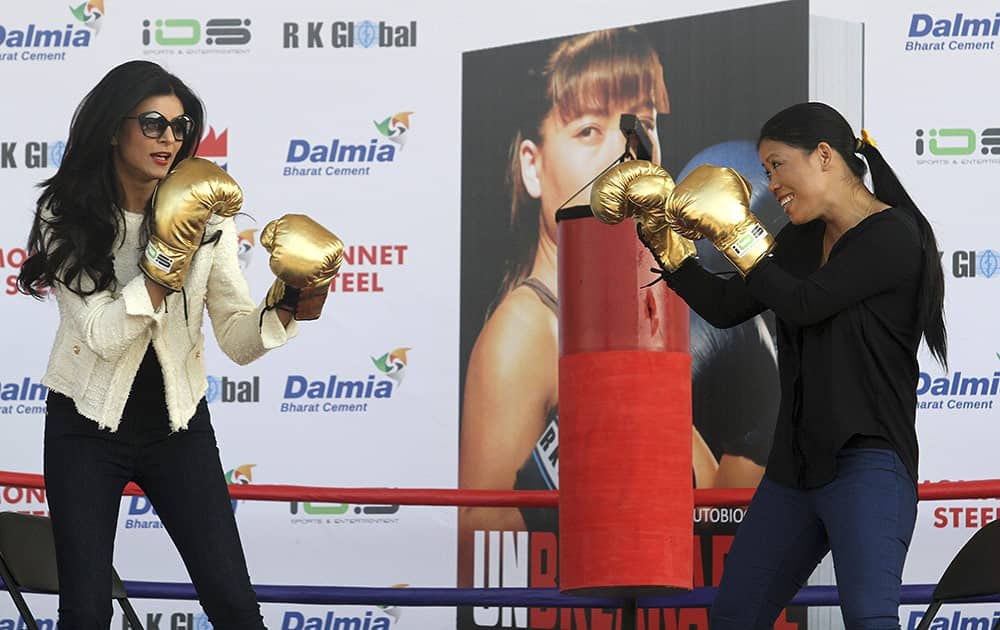Bollywood actress Sushmita Sen, left, and Indian boxer Mary Kom, right have a `friendly bout` during the release of the autobiography of Mary Kom, in Gauhati.