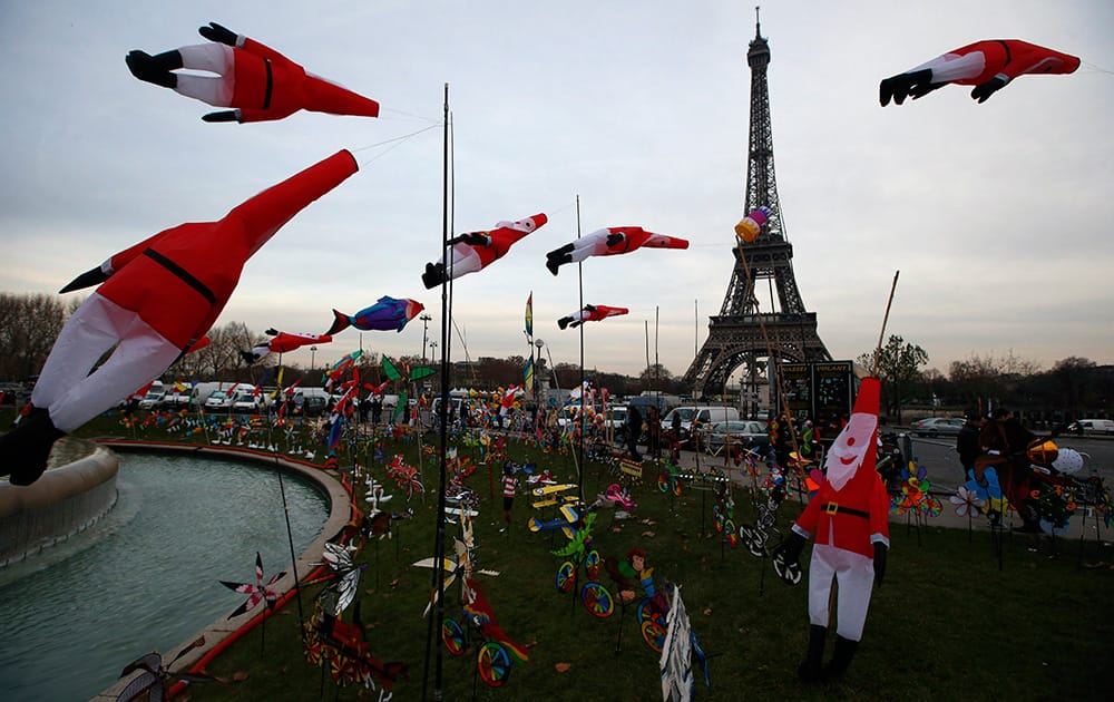 Kites in the shape of Santa Claus glide in the wind as part of a kite exhibition next to the Eiffel Tower in Paris.