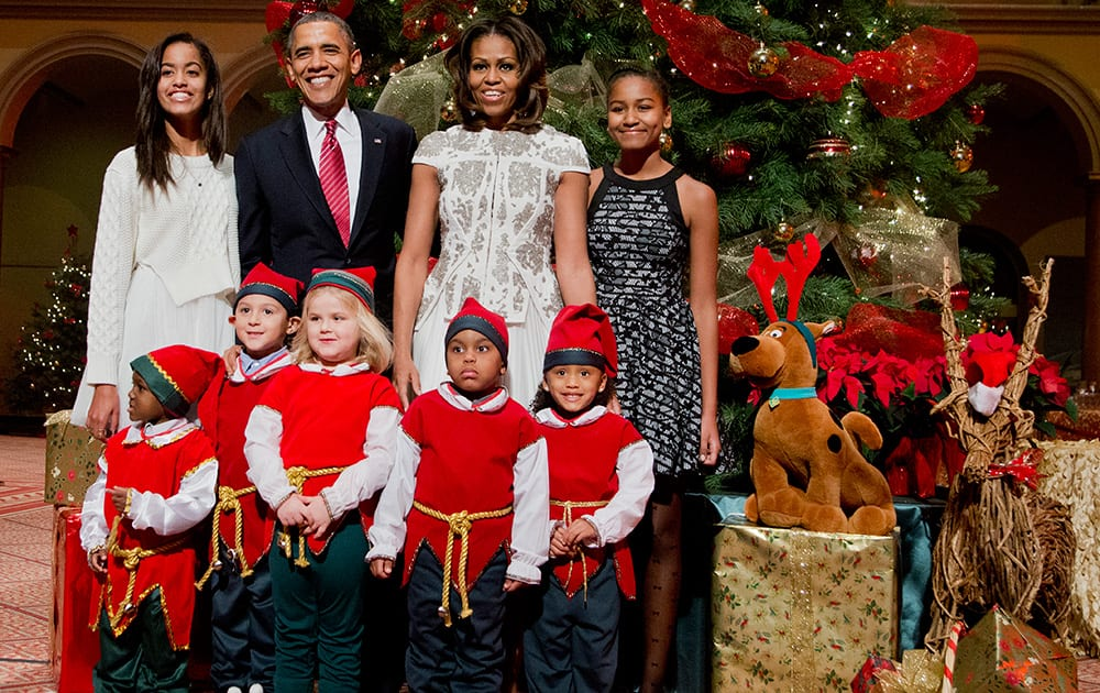 The first family, from left, Malia Obama, President Barack Obama, first lady Michelle Obama, and Sasha Obama, pose with children dressed like elves at the National Building Museum in Washington.