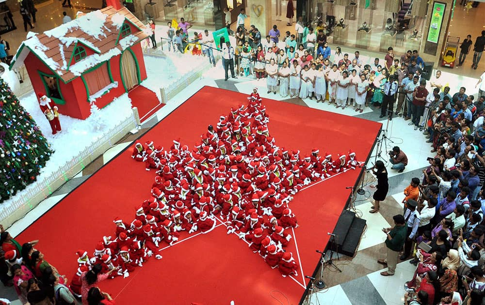 School children dressed as Santa Claus make a star during Christmas celebrations in Kochi.