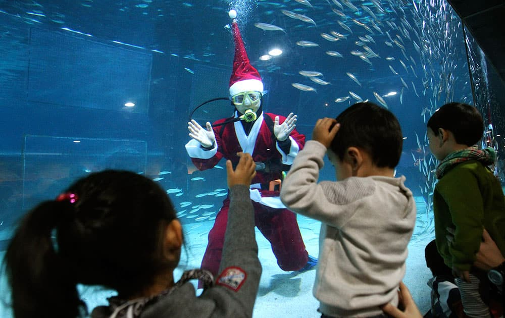 A diver dressed in a Santa Claus costume greets children at the Coex Aquarium in Seoul, South Korea.