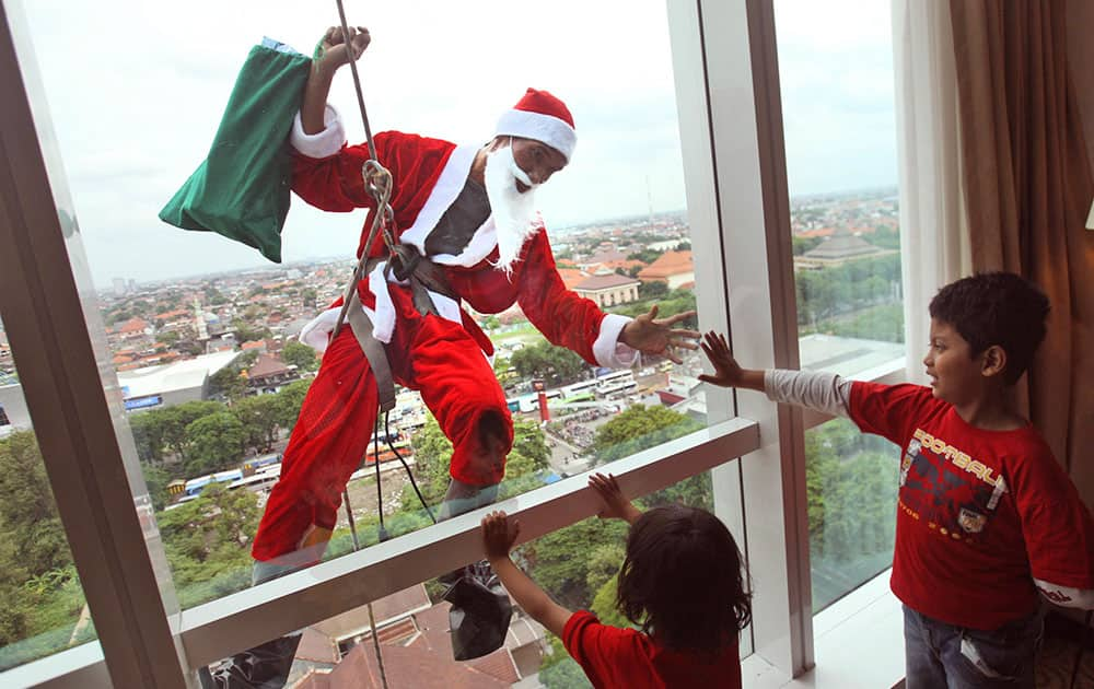 An employee in Santa outfit greets children as he rappels down from the roof of a hotel during a promotional event to celebrate Christmas in Surabaya, East Java, Indonesia.
