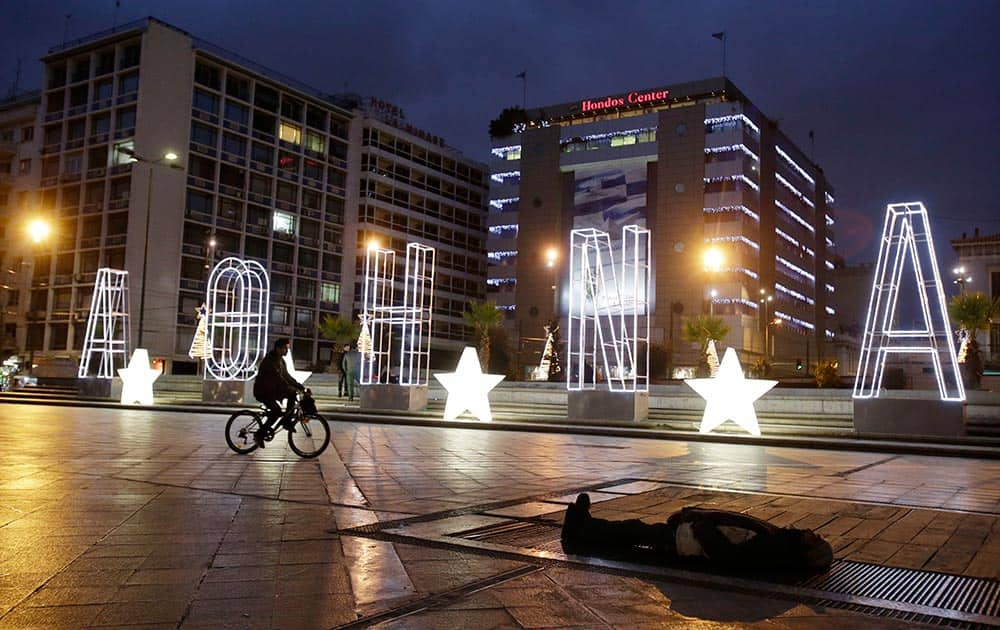A man rides his bicycle next to a lit Christmas sign reading ''Athens'' as a homeless man sleeps on a metro air vent above an underground station to warm up, at Omonia Square in central Athens.