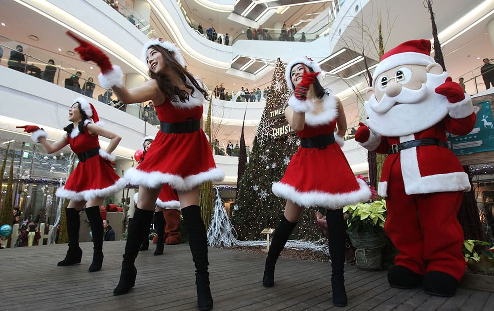 Employees dressed as Santa Claus perform as part of a shopping mall's Christmas celebrations in Seoul, South Korea.
