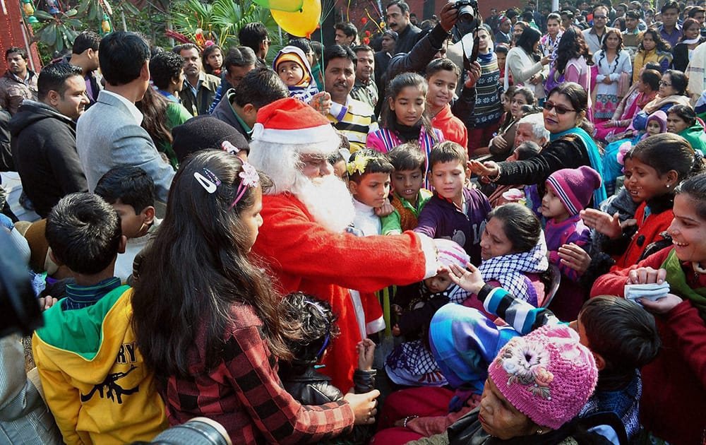 A man dressed up as Santa Claus distributing sweets among children on the occasion of Christmas in Moradabad.