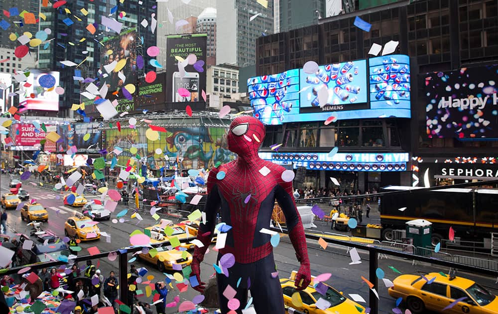 An actor portraying the comic book character Spiderman stands amidst falling confetti on the Hard Rock Cafe marquee during the annual confetti test in Times Square, New York.