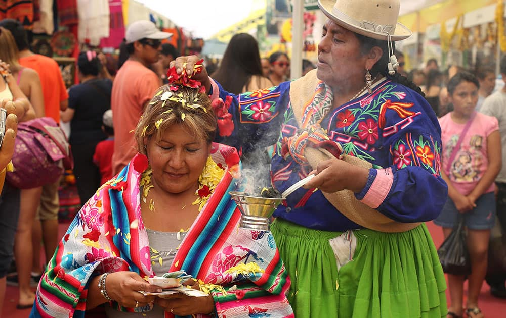 A shaman, right, performs a new year's ritual to bring good luck to her client for the coming year, at the Market of Wishes in Lima, Peru.