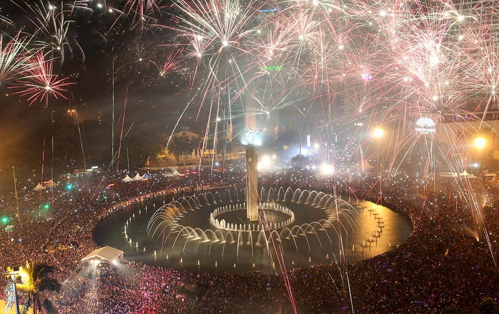 Fireworks light up the sky as thousands of people gather to watch, in the main business district on New Year's Eve in Jakarta, Indonesia.