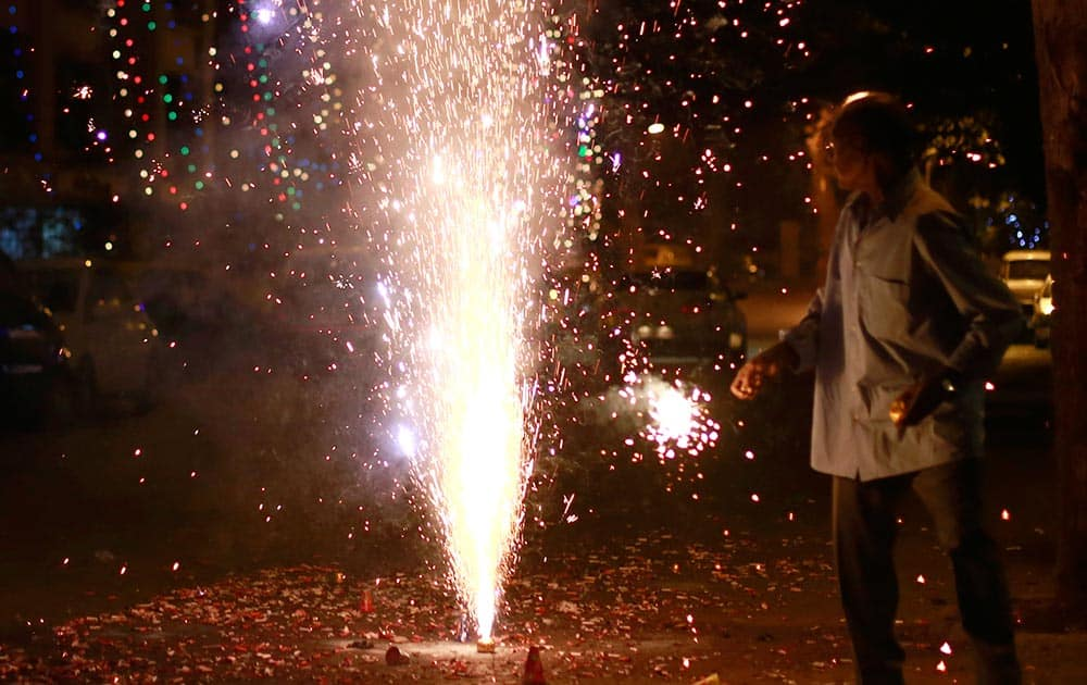 A man looks at fireworks on the street during the New Year celebration in Mumbai.