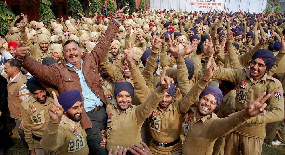 Policemen take part in a yoga laughter therapy session on the first day of New Year 2014 at Punjab Armed Police Acadamy in Jalandhar.