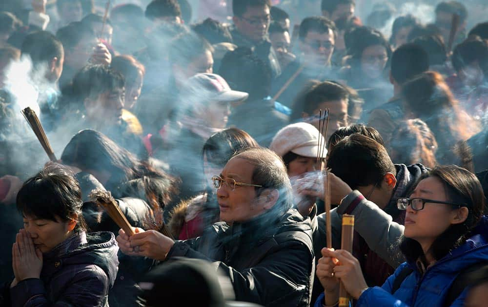 Chinese worshippers burn incense while offering prayers on the first day of the New Year at the Yonghegong Lama Temple in Beijing.