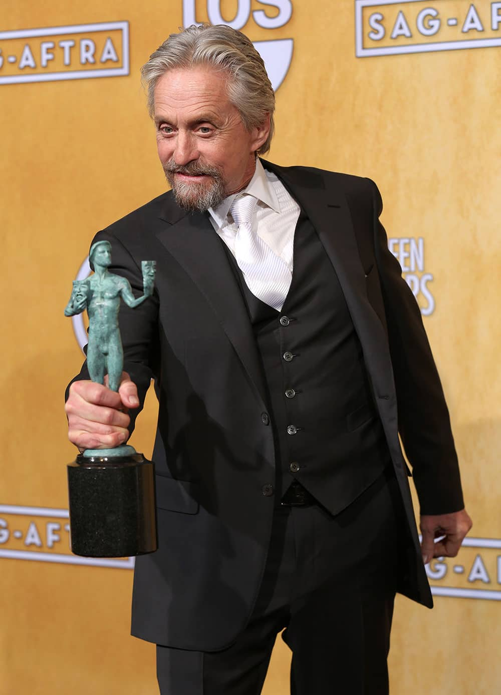 Michael Douglas poses in the press room with the award for outstanding performance by a male actor in a television movie or miniseries for `Behind the Candelabra` at the 20th annual Screen Actors Guild Awards at the Shrine Auditorium.