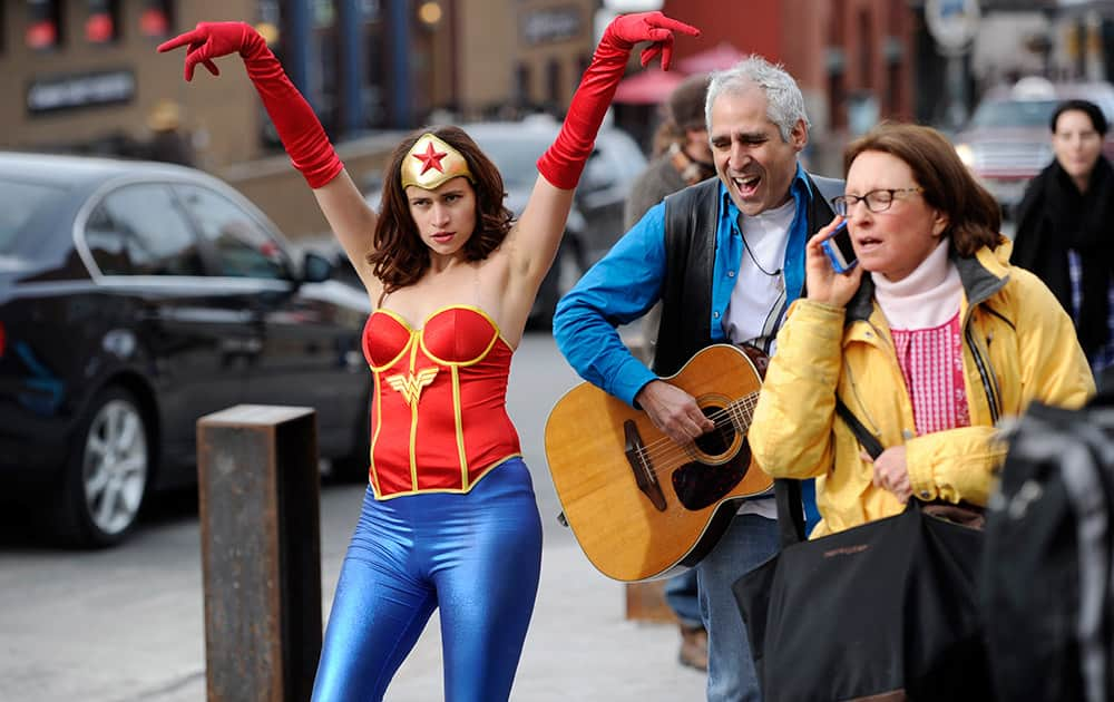 Sara Fischel, left, of Los Angeles, an actress and filmmaker working on a film called `The Adventures of Wonder Woman,` dances along with street musician Stewart Antelis, center, on Main Street during the seventh day of the 2014 Sundance Film Festival.