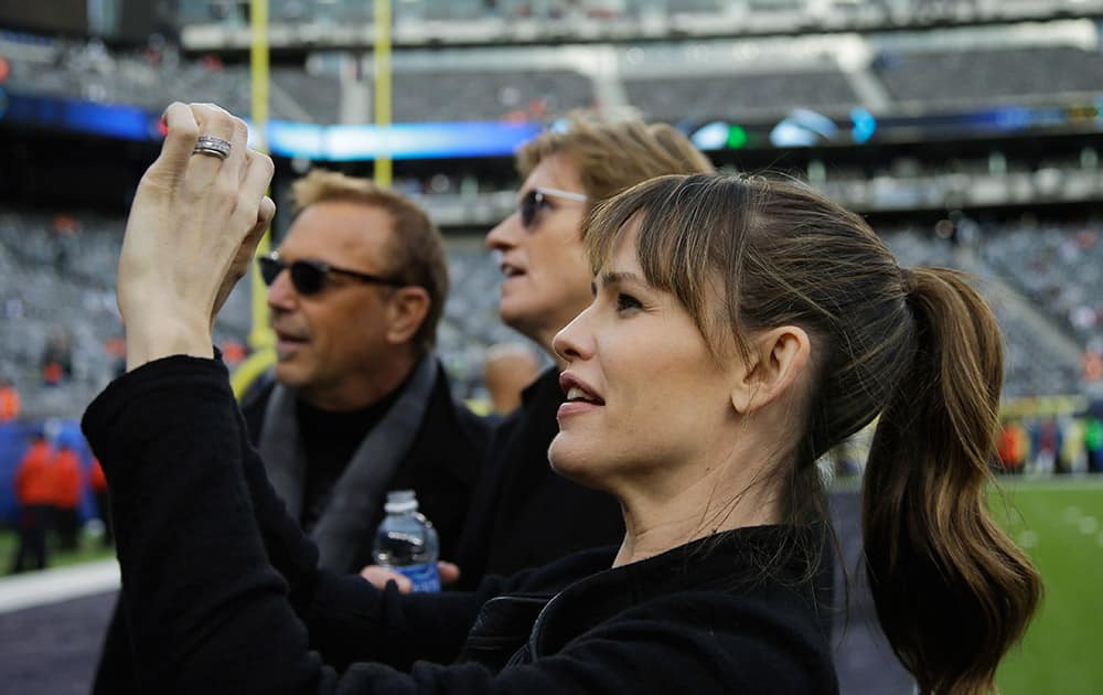 Actress Jennifer Garner takes a photo as actors Kevin Costner, left, and Denis Leary look on, at MetLife Stadium before the NFL Super Bowl XLVIII football game between the Seattle Seahawks and the Denver Broncos in East Rutherford, N.J.