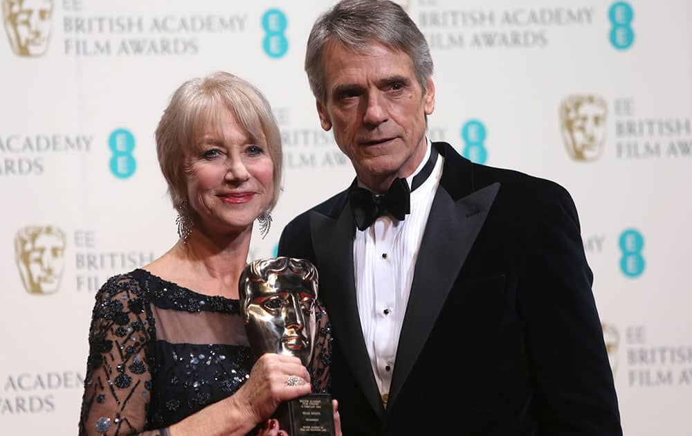 Dame Helen Mirren winner of outstanding contribution and Jeremy Irons poses for photographers in the winners room at the EE British Academy Film Awards held at the Royal Opera House.
