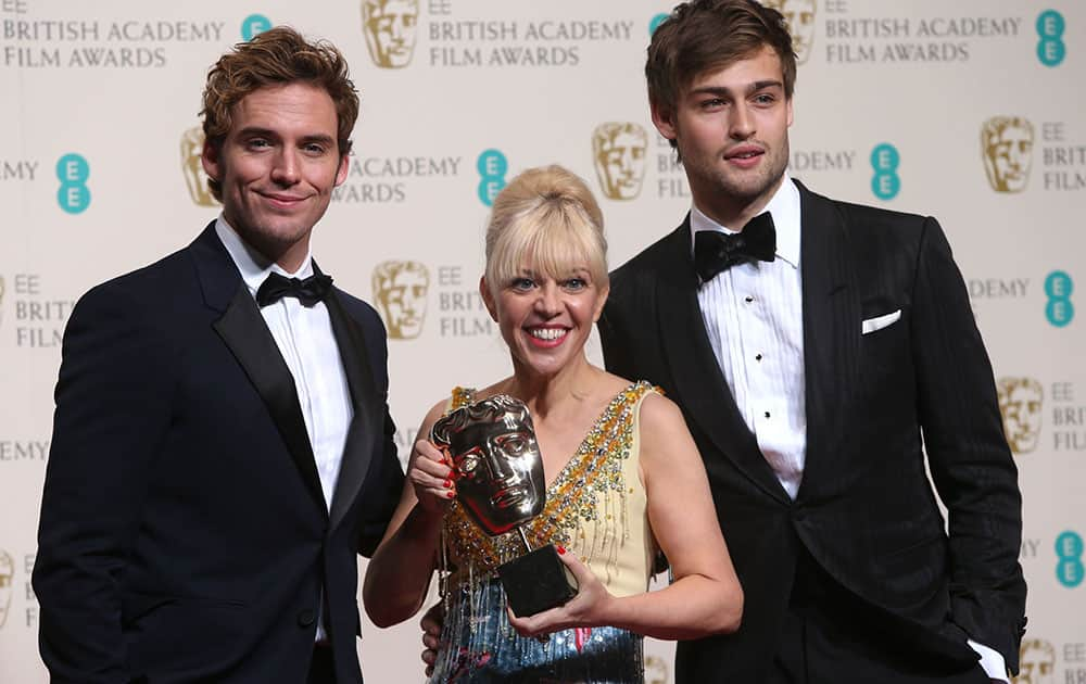 From left, Sam Claflin, Catherine Martin, winner of best costume design and Douglas Booth pose for photographers in the winners room at the EE British Academy Film Awards held at the Royal Opera House in London.
