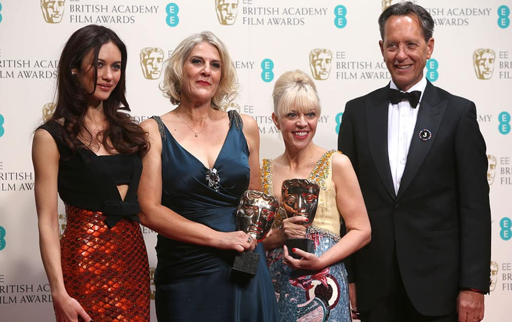 From left, Olga Kurylenko, Catherine Martyn, Beverley Dunn winners of best production design and Richard E Grant pose for photographers in the winners room at the EE British Academy Film Awards held at the Royal Opera House in London.