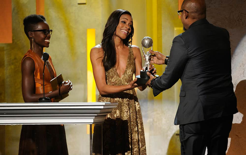From left, Lupita Nyong'o and Naomie Harris present Forest Whitaker with the award for outstanding actor in a motion picture for `Lee Daniels' The Butler` at the 45th NAACP Image Awards at the Pasadena Civic Auditorium in Pasadena, Calif.