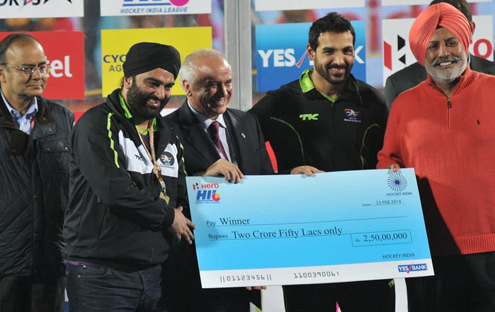 Actor and Co-owner of Delhi Waveriders John Abraham receives cheque after winning the HIL match against Japee Punjab Warriors in Ranchi.