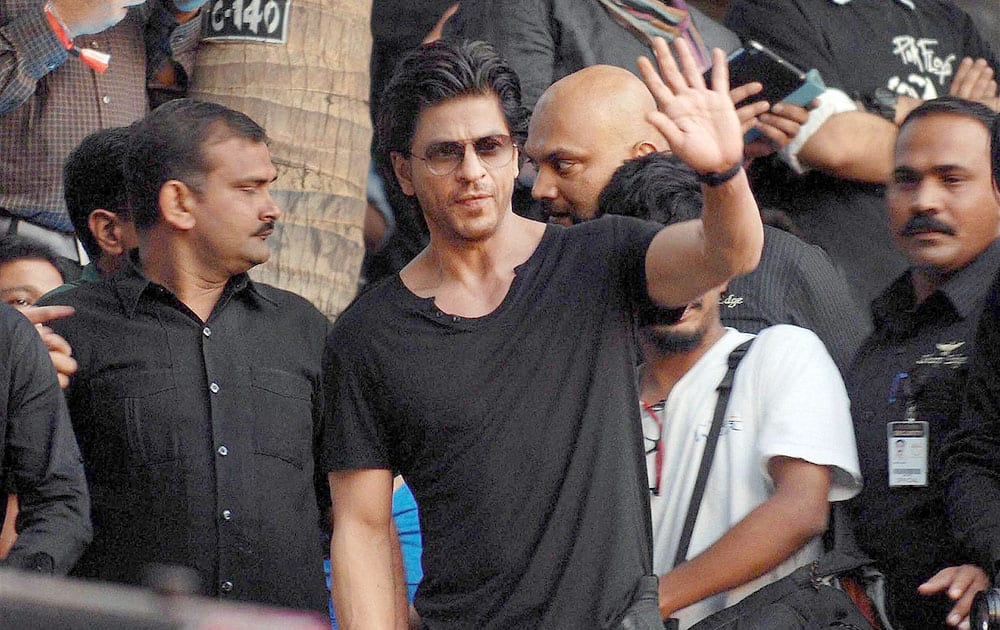 Bollywood actor Shahrukh Khan waves hands at the audience during an event in Mumbai.